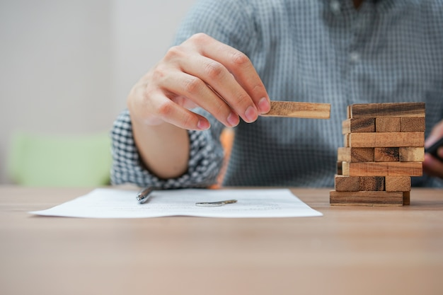 Close-up werknemer man hand met houten blok voor het spelen van het spel tijdens het werken