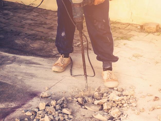 Close-up werknemer man metselaar boren cement betonnen vloer met machine