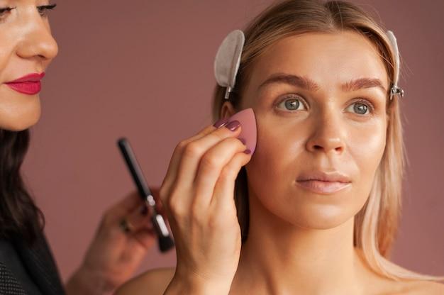 Close-up werkproces make-up artiest past huidskleur met spons make-up ei