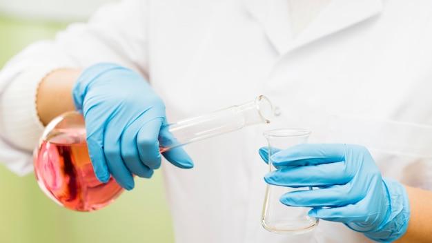 Close-up wetenschapper gieten oplossing in glas