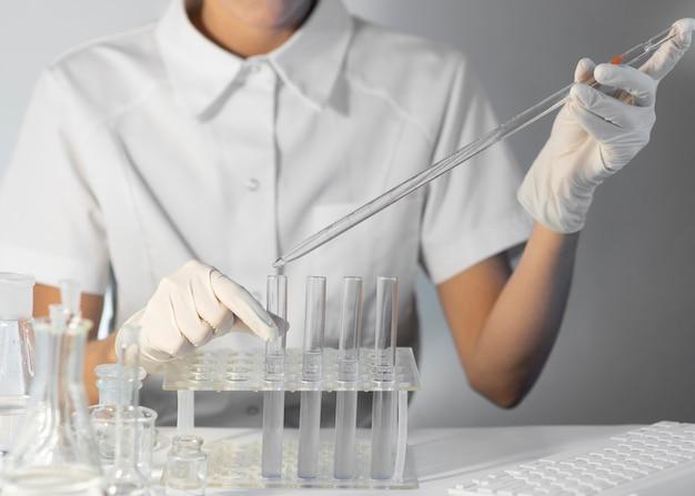 Close-up wetenschapper pipet en buis te houden