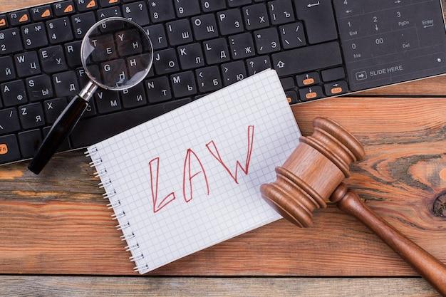 Close-up wetten woorden geschreven op spiraalvormige notitieblok hamer en vergrootglas op het toetsenbord