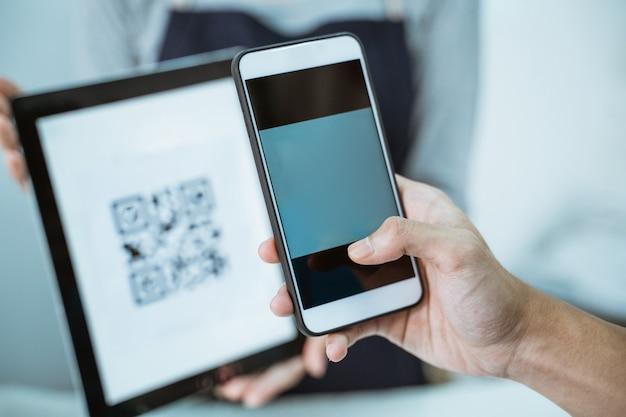 Close-up winkelier serveert klant qris barcode online betaling. focus op de telefoon van de klant