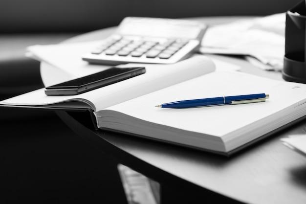Close-up witte memo notebook met blauwe pen en mobiele telefoon op zwarte ronde tafel.