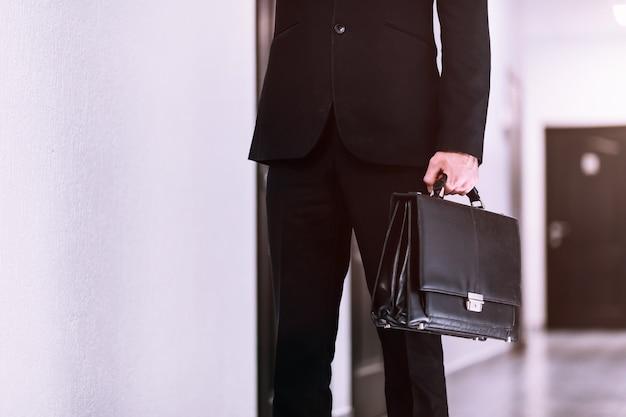 Close-up zakenman bedrijf aktetas op gang kantoor