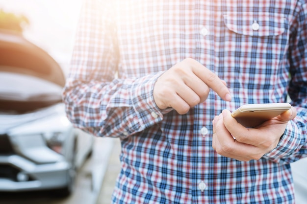 Close-up zakenman hand met behulp van een mobiele slimme telefoongesprek een automonteur om hulp vragen omdat de auto langs de weg is gebroken