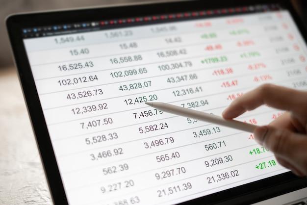 Close-up zakenman hand met pan kijkend door de details van de beurs op laptop