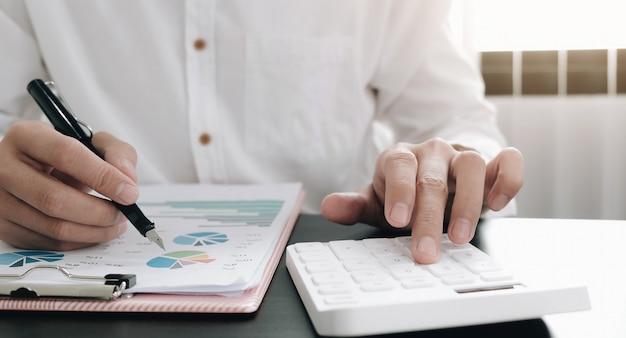Close-up zakenman met behulp van rekenmachine en het controleren van een grafiek op kantoor
