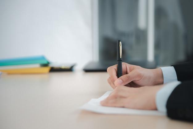 Close-up zakenman schrijven of ondertekenen contract op papier in kantoor.