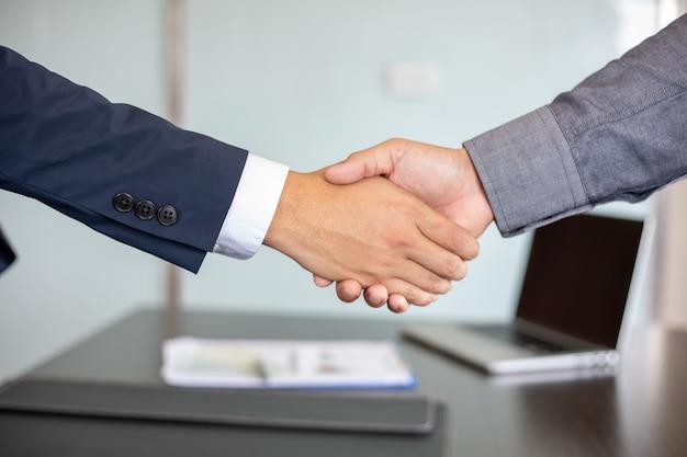 Close-up zakenmensen die handen schudden en glimlachen om hun overeenkomst om het contract te ondertekenen en een vergadering af te ronden