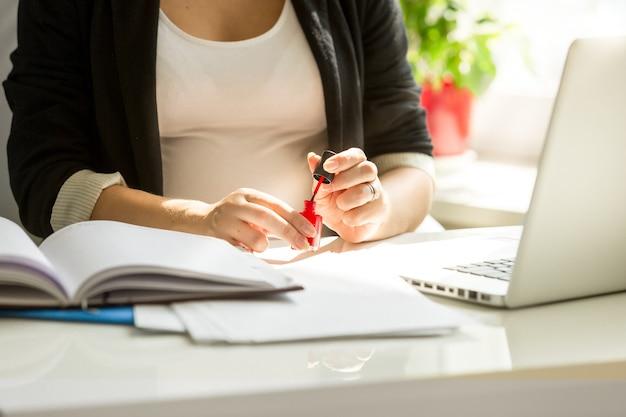 Close-up zakenvrouw die vingernagels schildert aan kantoortafel