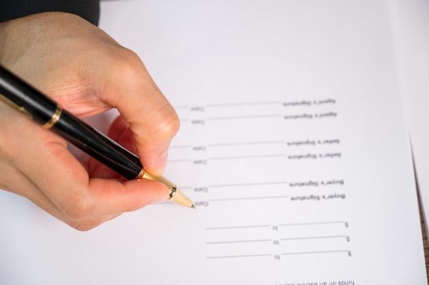 Close up zakenvrouw hand teken contract document aan de balie in een kantoor