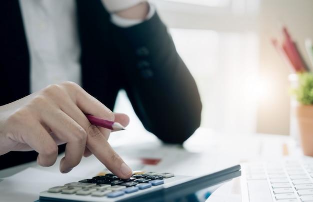 Close-up zakenvrouw met behulp van calculator en laptop voor wiskunde financieren op houten bureau in kantoor en zakelijke werken, belasting, boekhouding, statistieken en analytisch onderzoek concept