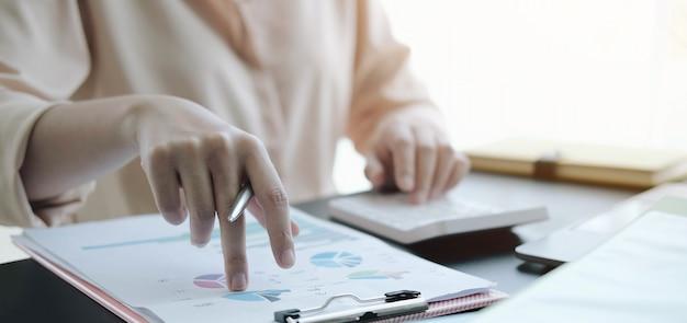 Close-up zakenvrouw met behulp van rekenmachine en het controleren van een grafiek op een houten bureau op kantoor