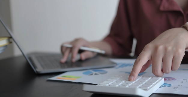 Close-up zakenvrouw met behulp van rekenmachine en laptop op houten bureau op kantoor