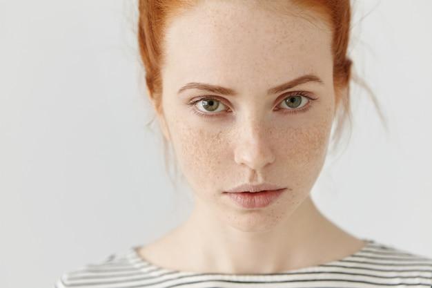 Close-up zeer gedetailleerd beeld van mooie charmante jonge vrouw met een perfecte sproetige huid, rood haar en groene ogen die binnenshuis rusten
