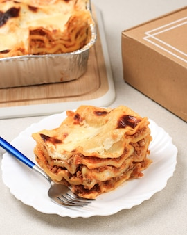 Close-up zelfgemaakte heerlijke gesneden lasagne op witte plaat, heerlijke laag italiaans eten