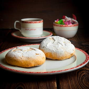 Close-up zelfgemaakte koekjes met kopje thee en snoepjes op houten tafel
