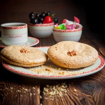 Close-up zelfgemaakte koekjes met kopje thee, snoepjes en bessen op houten tafel