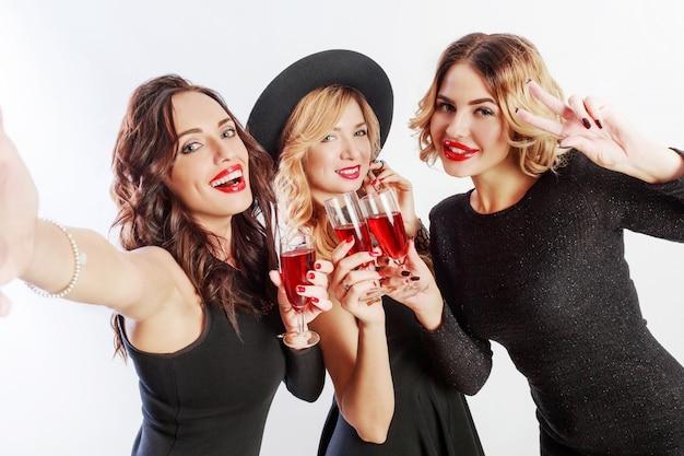 Close-up zelfportret van drie mooie vrouwen vieren vrijgezellenfeest en cocktails drinken. beste vrienden die zwarte avondjurk en hakken dragen. lichte make-up, rode lippen. binnen.