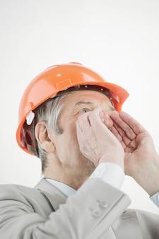 Close-up. zelfverzekerde senior ingenieur schreeuwen. geïsoleerd op een witte muur.