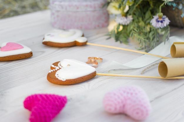Close-up zicht op hartvormige koekjes koekjes op stok en trouwringen.