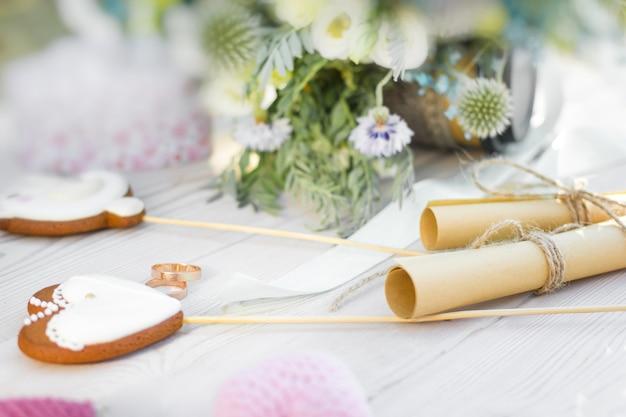 Close-up zicht op trouwringen en twee opgerolde vellen papier met huwelijksgeloften hartvormige koekjes