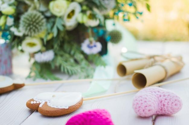 Close-up zicht op twee opgerolde vellen met bruidsgeloften koekjes bisquites en bruidsboeket