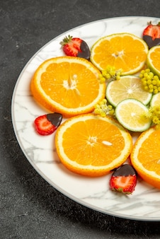 Close-up zijaanzicht aardbeien en oranje bord met sinaasappelcitroen en met chocolade omhulde aardbeien op de donkere achtergrond