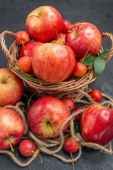 Close-up zijaanzicht appels appels de smakelijke kersen in de mand