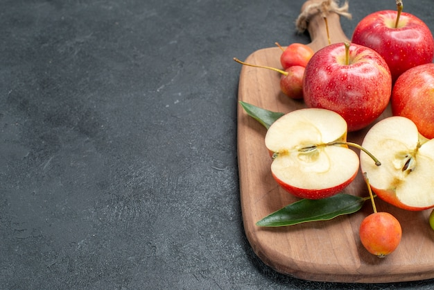 Close-up zijaanzicht appels de smakelijke bessen en vruchten op het houten bord