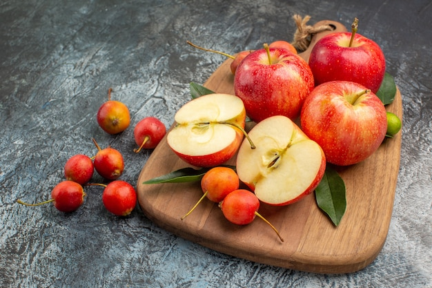 Close-up zijaanzicht appels de snijplank met appels kersen met bladeren