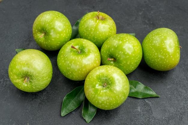 Close-up zijaanzicht appels zeven smakelijke groene appels met bladeren op tafel