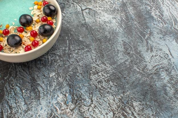 Close-up zijaanzicht bessen de smakelijke rode aalbessen druiven op de grijze tafel
