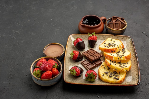 Close-up zijaanzicht cake met aardbeien smakelijke cake met chocolade bedekte aardbeien en chocolade crème aardbei en chocolade in kommen op de donkere achtergrond