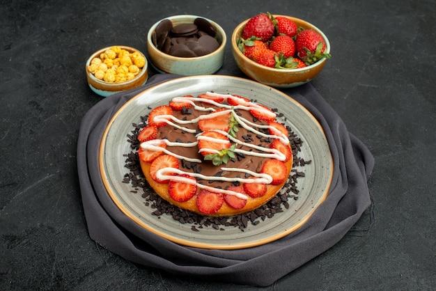 Close-up zijaanzicht cake op tafelkleedtaart met chocolade en aardbeienstukjes op grijs tafelkleed naast kommen hazelnootaardbei en chocolade en cake op zwarte tafel