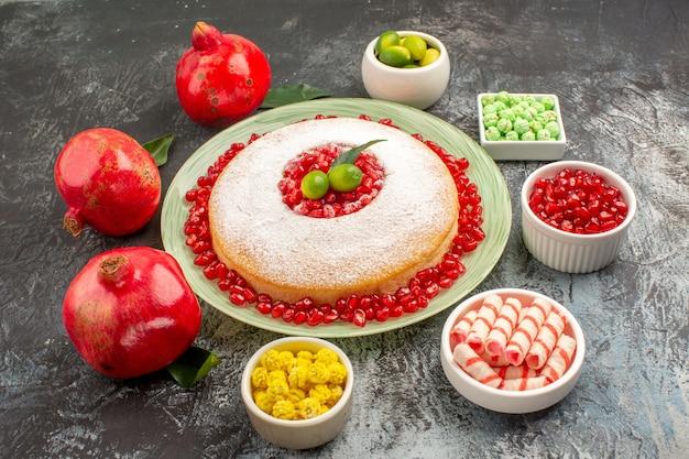 Close-up zijaanzicht cake snoepjes een bord cake granaatappels kommen citrusvruchten kleurrijke snoepjes