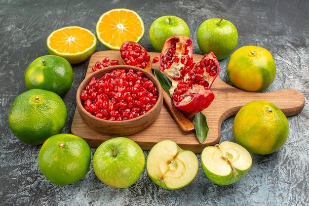 Close-up zijaanzicht citrusvruchten appels mandarijnen granaatappel zaden op het bord