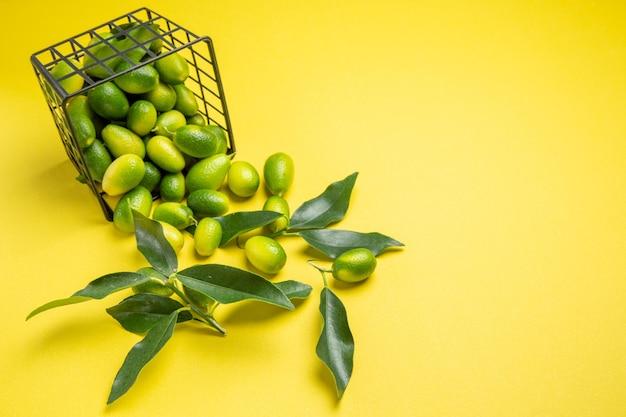 Close-up zijaanzicht citrusvruchten grijze mand met citrusvruchten met bladeren op de gele achtergrond