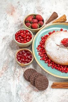 Close-up zijaanzicht de smakelijke cake de smakelijke cake naast de kommen met bessenkoekjes