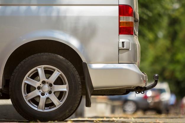 Close-up zijaanzicht detail van zilveren passagier middelgrote luxe minibus met trekhaak geparkeerd op straat van de zomer zonnige stad met wazig silhouetten van voetgangers en auto's op de achtergrond.