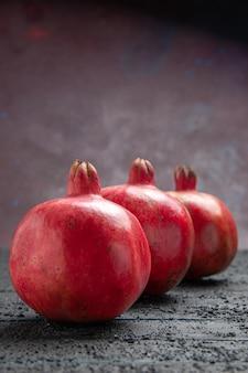 Close-up zijaanzicht drie granaatappels op donkere achtergrond drie granaatappels op donkere achtergrond