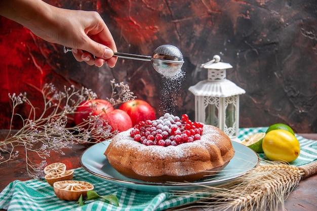 Close-up zijaanzicht een cake een cake met rode aalbessen, citroenen, appels, lepel in de hand