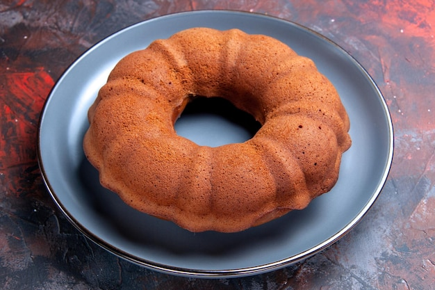 Close-up zijaanzicht een smakelijke cake een smakelijke cake op het blauwe bord op de donkere tafel