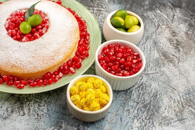 Close-up zijaanzicht een smakelijke cake een smakelijke cakekommen met bessen en drie granaatappels