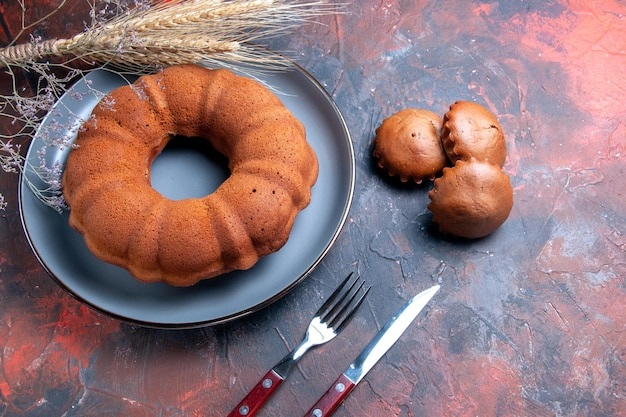 Close-up zijaanzicht een taartvork mes tarweoren takken een smakelijke cake en cupcakes