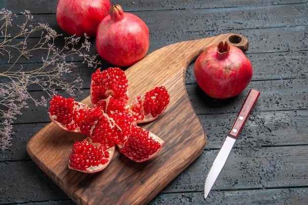 Close-up zijaanzicht gepilde granaatappel en takken gepilde granaatappel op keukenbord naast boomtakken mes en drie granaatappels op donkere tafel