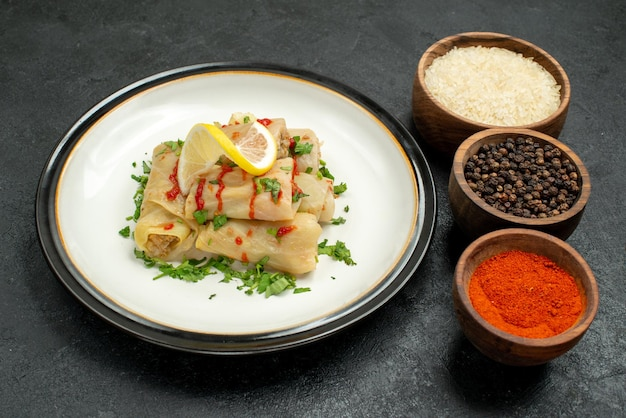 Close-up zijaanzicht gevulde kool plaat van gevulde kool met citroen kruiden en saus en kommen rijst kleurrijke kruiden en zwarte peper op zwarte tafel