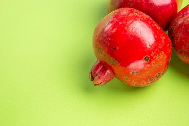 Close-up zijaanzicht granaatappel de smakelijke granaatappels op de groene achtergrond