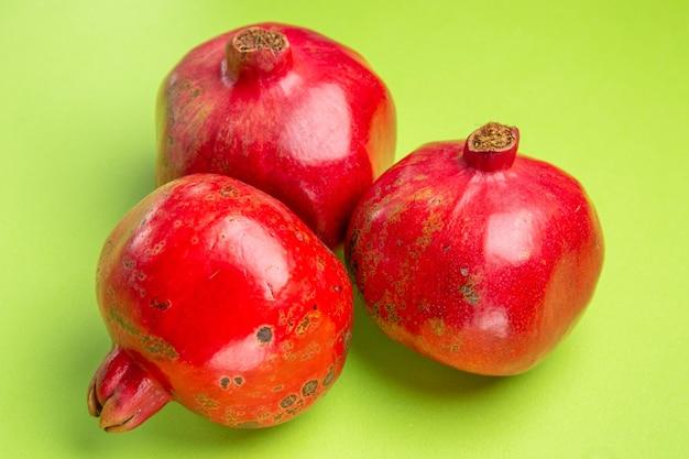 Close-up zijaanzicht granaatappels drie granaatappels op het groene oppervlak
